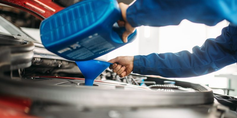 Technician change oil in the car engine